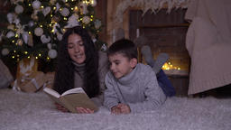 Mom with long hair reads a book to her son and kisses him lying on the floor Footage