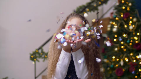 Joyful little girl blowing out confetti from palms GIF