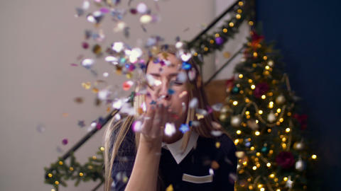 Cheerful woman blowing colorful confetti from hand Footage