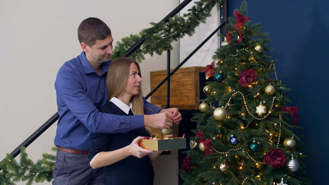 Couple decorating Christmas tree with baubles Footage