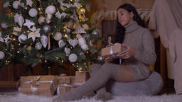 Girl puts a box with a gift near the Christmas tree.HD Footage