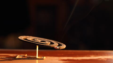Violet mosquito repellent and white smoke on wooden table with black light space フォト