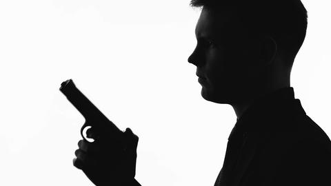 Silhouette of male serial killer holding gun, preparing to shoot, crime and law Live Action