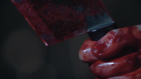 Bloody hand holding knife, slayer trembling with anger, shocked and scared Footage