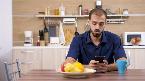 Man at the table in the kitchen using a smartphone GIF