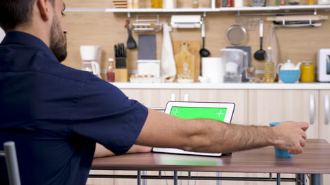 Man at the kitchen looking at digital tablet PC Live Action