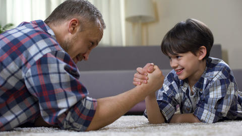 Little male kid challenging his father in arm wrestling, having fun together Footage