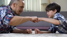 Stepfather and child fist bumping, partnership greeting, happy childhood moment Footage