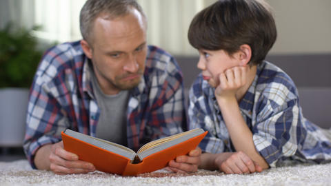 School boy listening to dad reading exciting adventure book, love to literature Footage