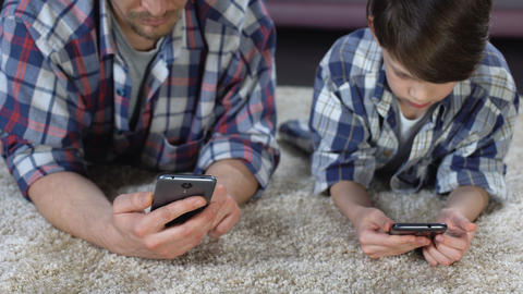 Son and his father lying down on floor playing on smartphones, lack of care Footage