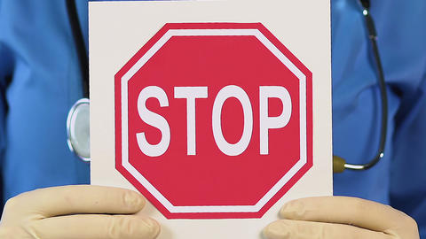 Medical worker holding stop sign, calling to stop spreading virus, vaccination Live Action