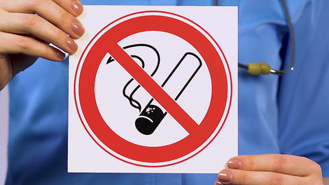 Doctor holding sign prohibiting smoking, clinic for treatment of addicted people Live Action