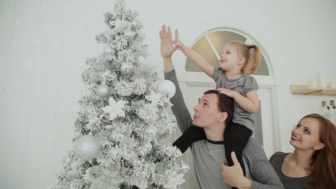 The family is standing near the Christmas tree, laughing talking and touching Footage
