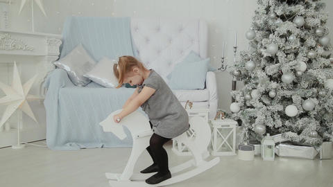 Very beautiful little girl riding on a wooden horse in the New Year's room and GIF