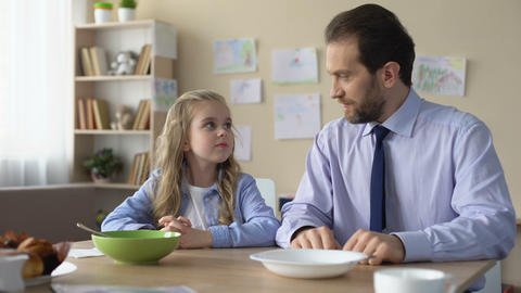 Pretty girl and her father praying before eating breakfast, spiritual education Live Action