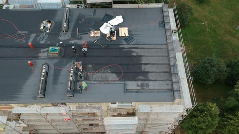 Two workers repair flat house roof in city, aerial view Live Action