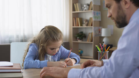Strict dad talking to daughter doing homework, parental control, education Live Action