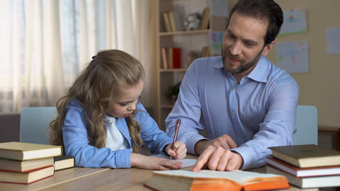 Attentive father helps his little daughter to do homework for school, education Live Action