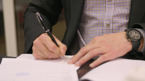 Businessman doing paperwork in the office. Young male filling checklist sitting GIF