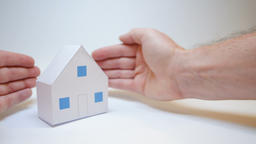 paper house symbolizing the family is protected by the hands of an accident Live Action