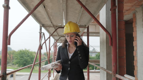 Female Engineer Talking On Mobile Telephone In Construction Site Live Action