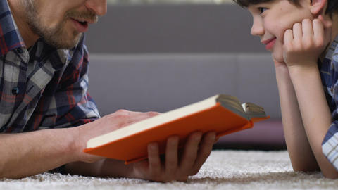 Father reading fairytale to son lying on floor, home leisure preschool education Footage