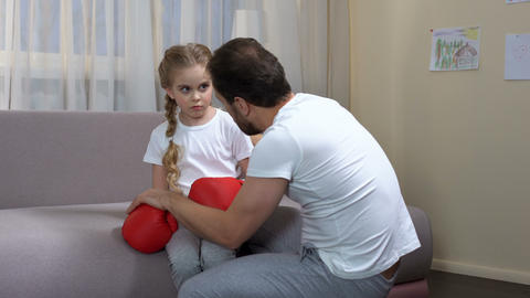 Dad calming down daughter after box game, trusting relationship, trainer support Footage