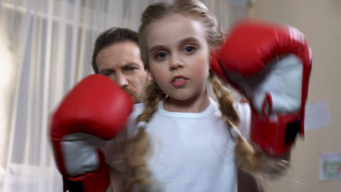 Boxing school girl practicing punches with father at home, self-defense lesson Footage