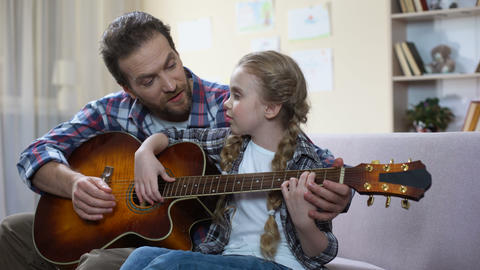 Father teaching daughter to play guitar at home, musical hobby, family leisure Live Action