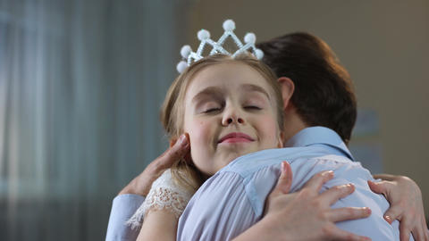 Cute little girl in princess crown dress hugging father, tender relations, party Live Action