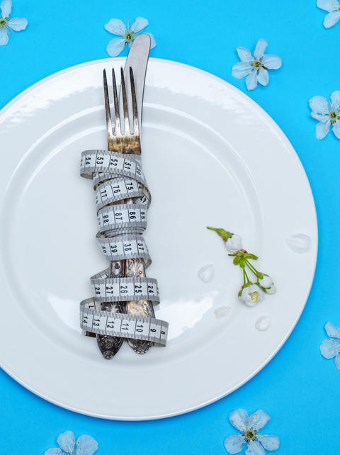 fork with a knife wrapped in a measuring tape lie on a white rou Fotografía