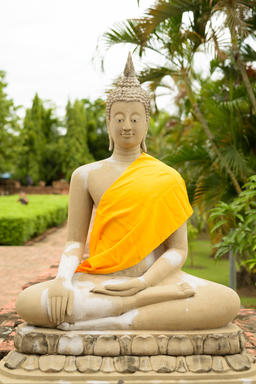 Sculpture of Buddha wearing yellow robe while meditating in Ayut Photo