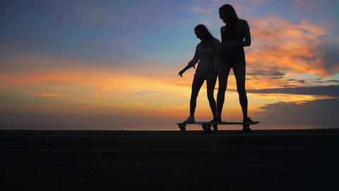Two girlfriend girls in shorts and sneakers ride skateboards on the slope Live Action