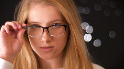 Relaxed blonde caucasian girl in glasses with smart look , touching her glasses Footage