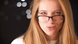 Beautiful caucasian blonde girl is strengthening her spectacles with third Footage