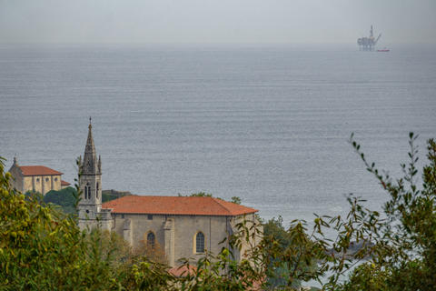 Mundaka church with gas ocean platform in the horizon Photo