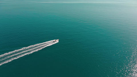 Motor boat floats in endless blue sea. Rippling water shine in the sun. Aerial Footage