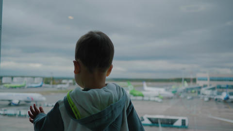 Little boy in airport looks on support vehicles and cloudy sky through window Footage