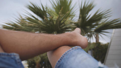 Legs of barefoot man sitting under palm tree. Relaxing... Stock Video Footage