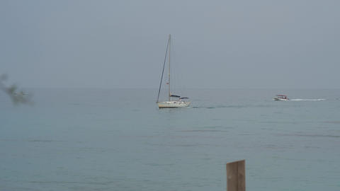 Sailing yacht and motor boat float on calm blue sea. Slow motion Live Action