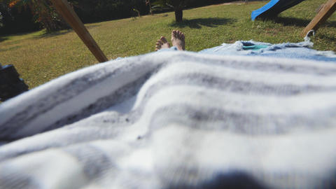 Hairy legs of a barefoot man who swings up and down. First person view GIF