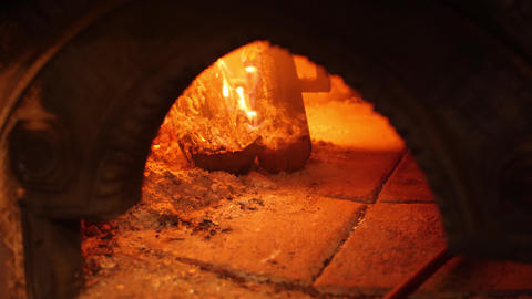 Burning fire in stone oven and pizza is baked near it. Traditional italian Live Action