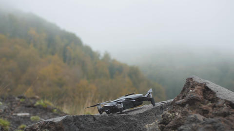 Drone takes off from rough stone in misty mountains. Fog in autumn forest 영상물