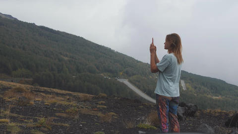 Young woman with cellphone takes panaramic photo of mountain in grey clouds Live Action