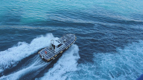 Pilot boat float fast from ferry towards the seaside city. Deep blue sea GIF