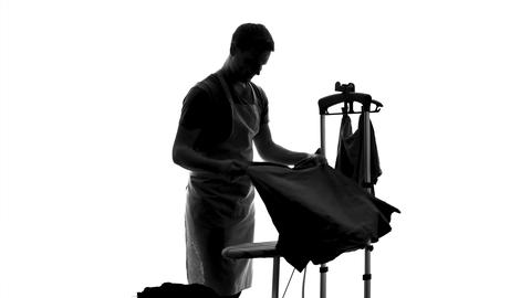 Smiling male householder ironing clothes on board, sharing of housework duties Footage