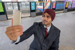 Indian businessman sitting at train station while taking selfie with mobile Photo