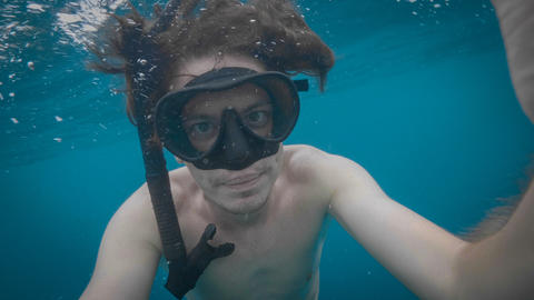 A young caucasian snorkeling man underwater selfie フォト