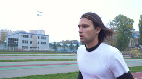 Young guy in a sports t-shirt runs in the stadium Handsome guy with dark hair Footage