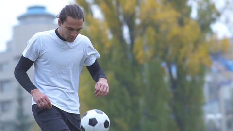 Young man in sportswear playing with a ball outdoors Sports guy playing with a Footage